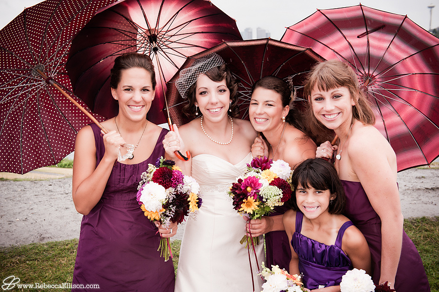 bridesmaids pose under bella umbrellas at a rainy seattle outdoor wedding