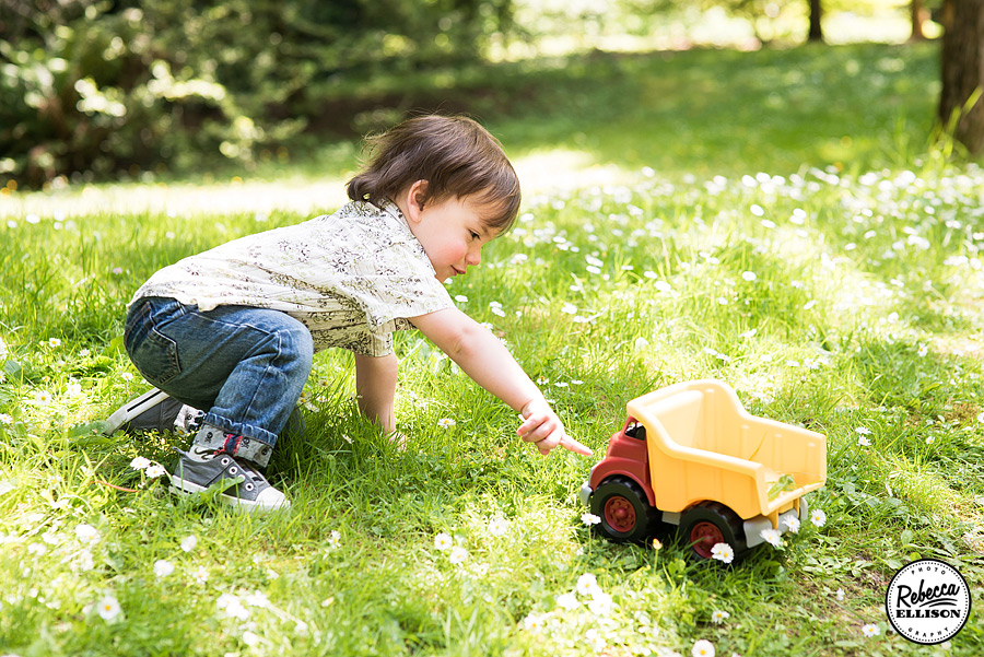 Boy and his truck in the grass during Seattle arboretum portraits by Seattle family photographer Rebecca Ellison