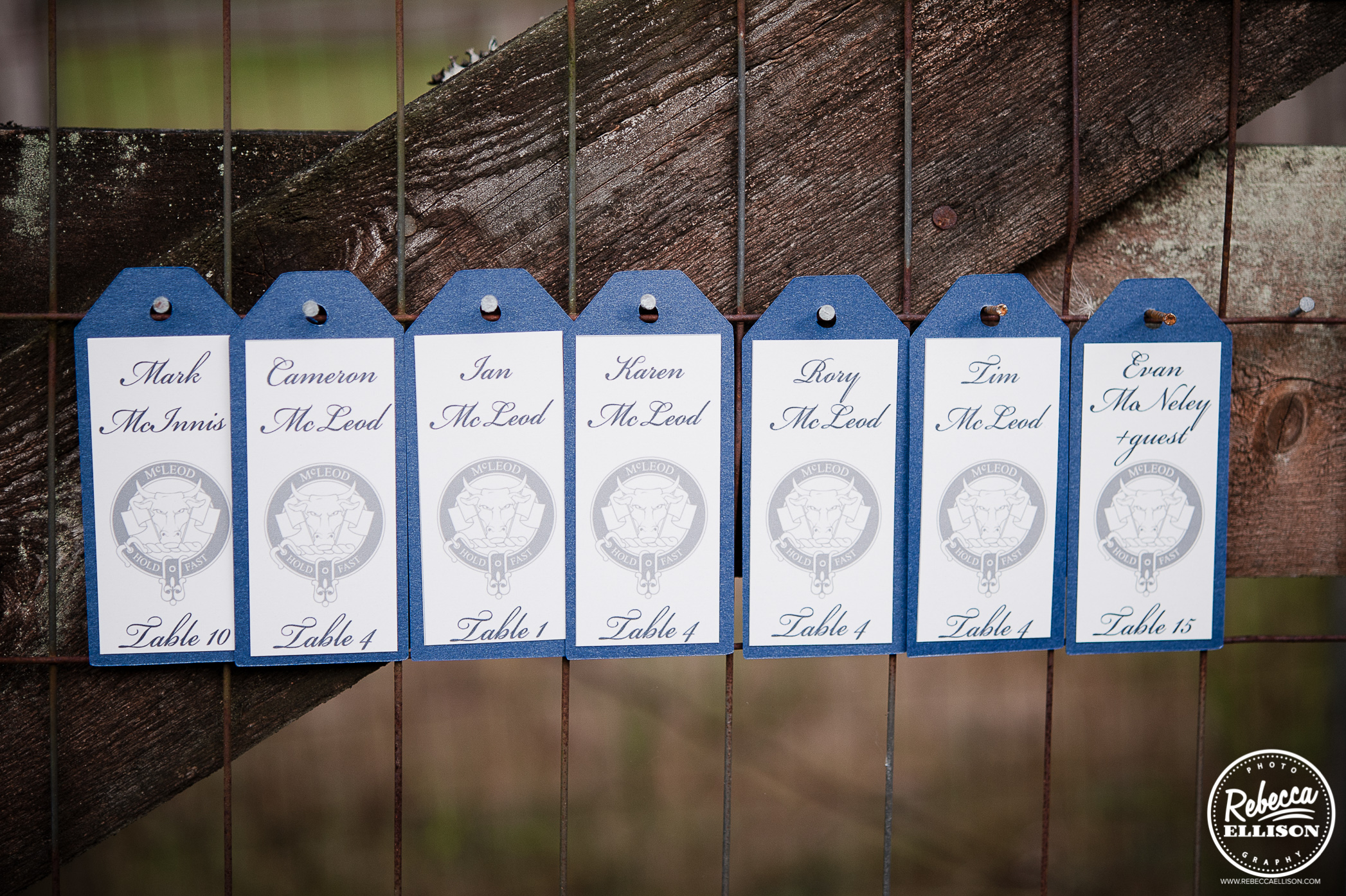 creative seating cards for wedding. tags on nails of a fence