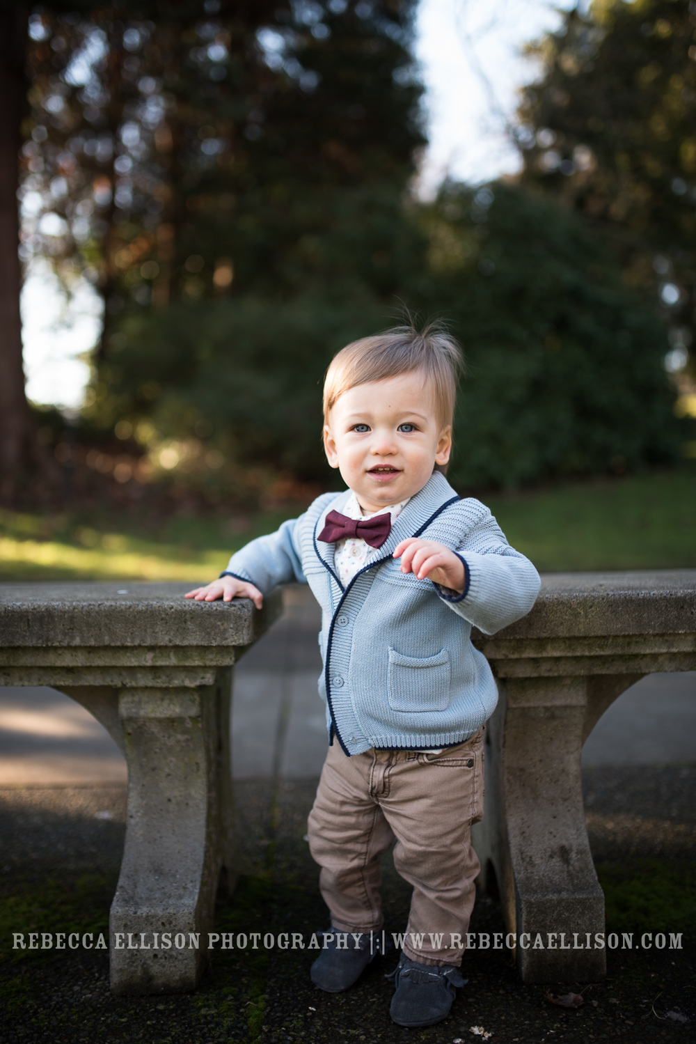 one year old stands in bow tie between benches at park