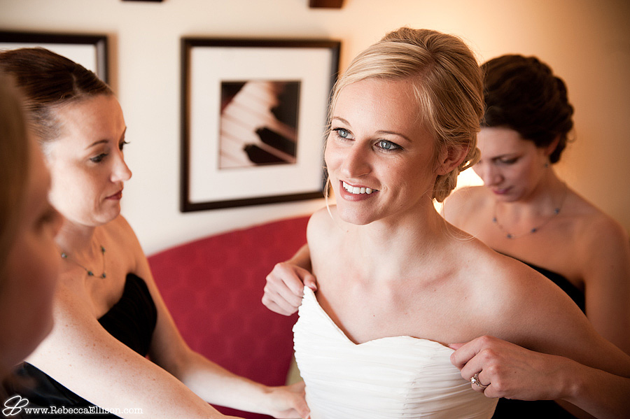 bride smiles at her bridesmaid while getting on her wedding dress