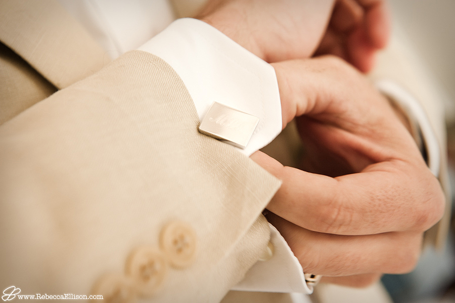 a groom fastens his custom cufflink before his wedding