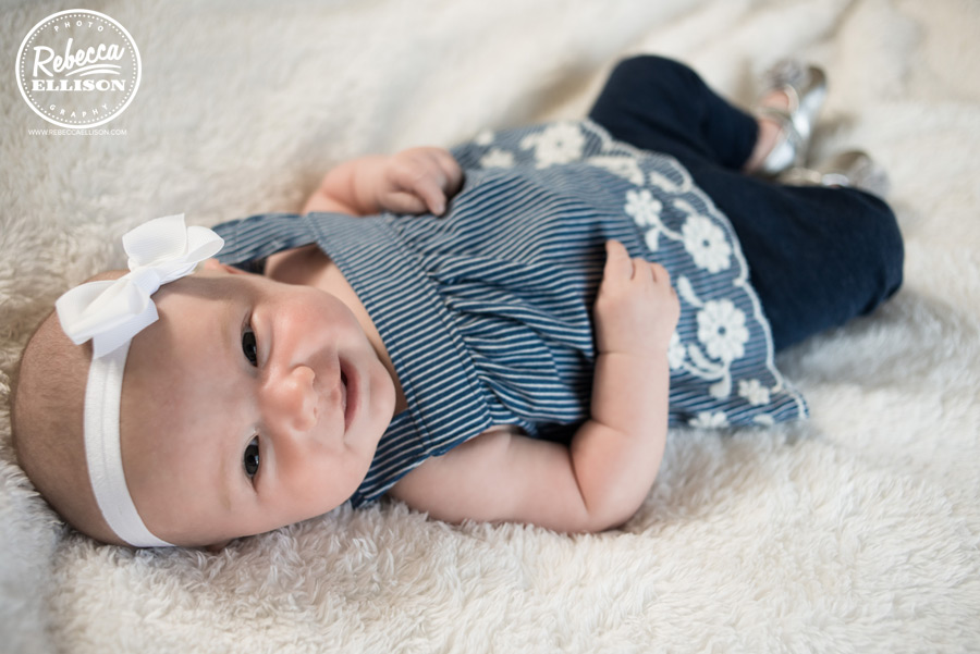 Baby girl in a blue and white outfit during a Seattle newborn portraits session by Seattle baby photographer Rebecca Ellison