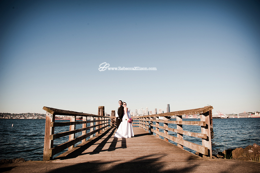 bride and groom pose on a dock at Alki with Seattle skyline in background