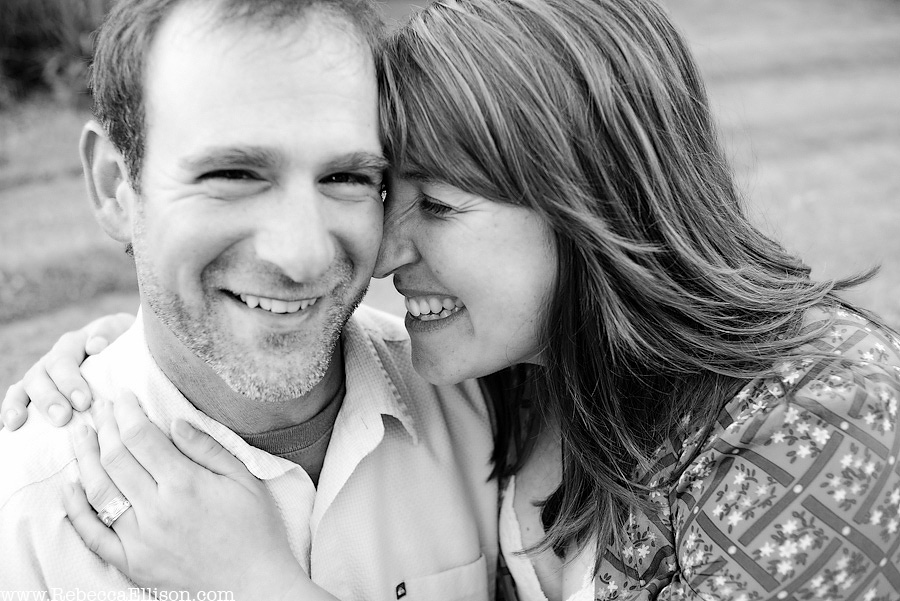black and white portrait of engaged couple smiling with her touching her forehead to his temple.
