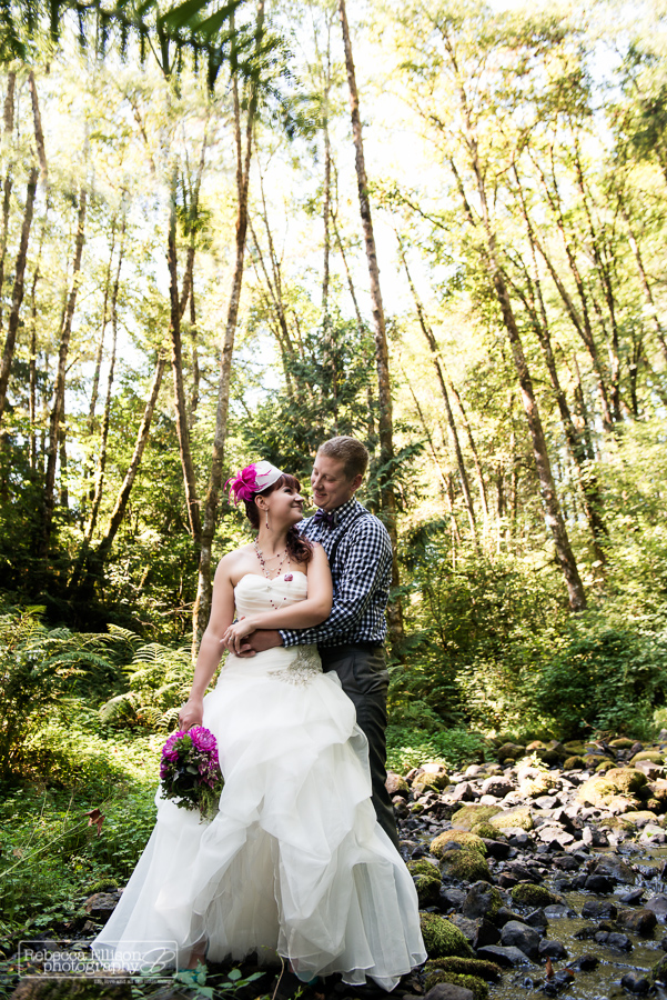 bride and groom stand in woods by creek smiling at each other