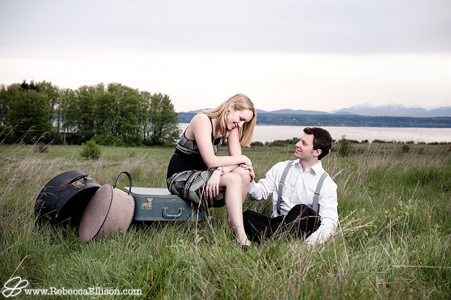 discovery park engagement photos, couple sitting on vintage luggage in field