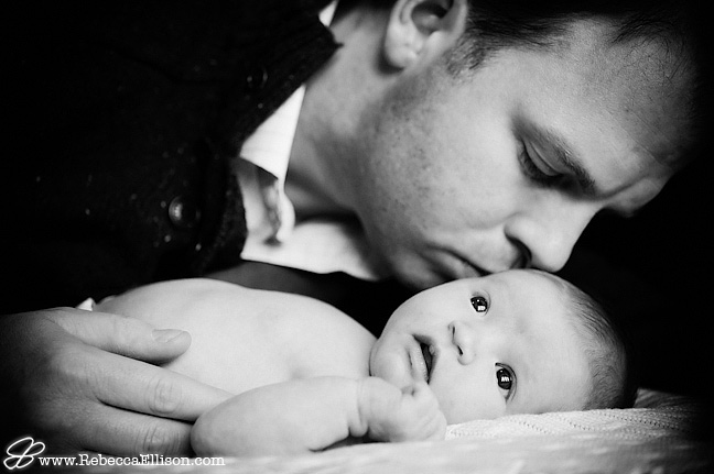 dad kissing newborn daughter portrait