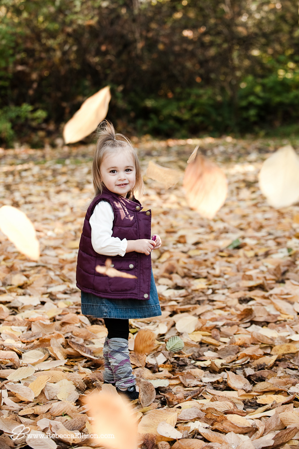 girl standing in falling fall leaves