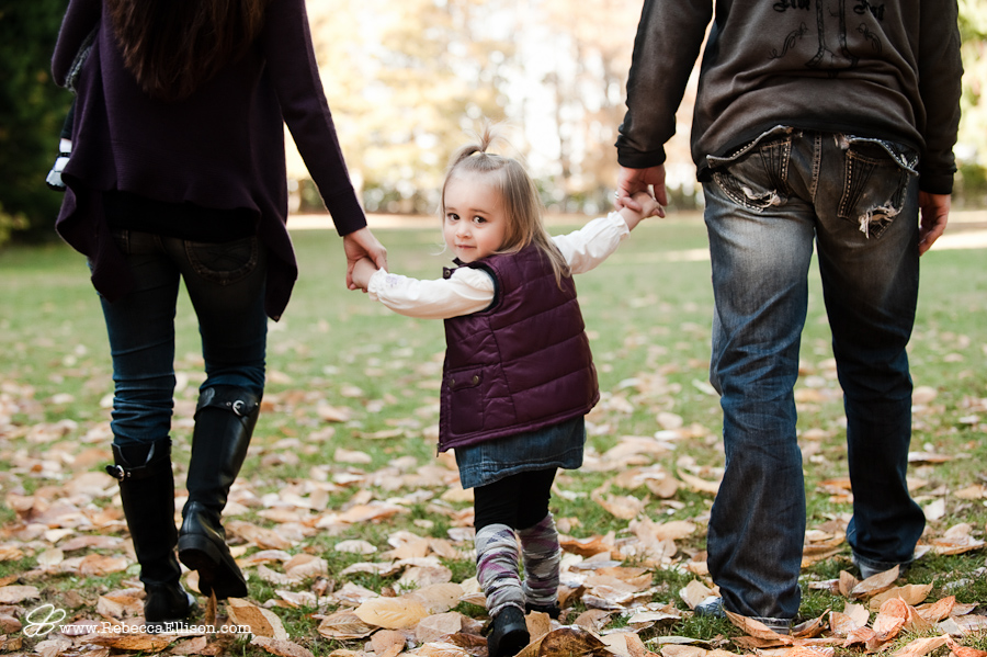 girl holding hands with parents looking back at camera while they walk away