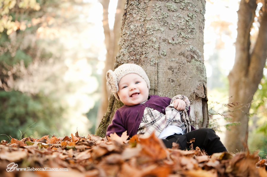 infant girl propped up against tree in fall leaves smiling at camera with cute knit hat