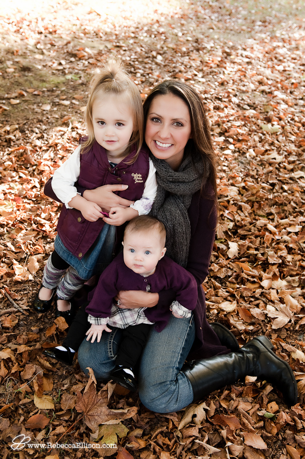 mom and daughters in fall leaves