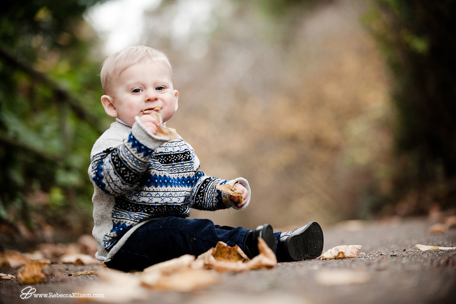 boy tries to eat leaf in fall outside portrait
