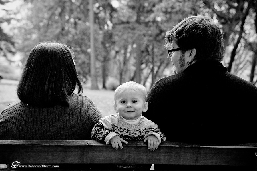 smiling baby boy on bench with parents