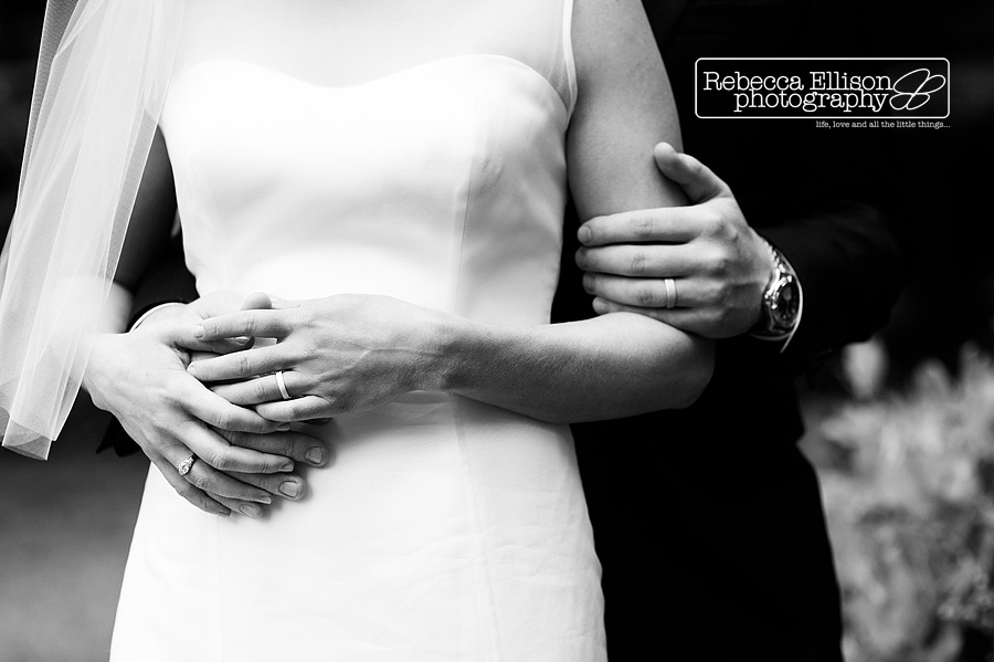 bride and groom embrace showing their wedding rings