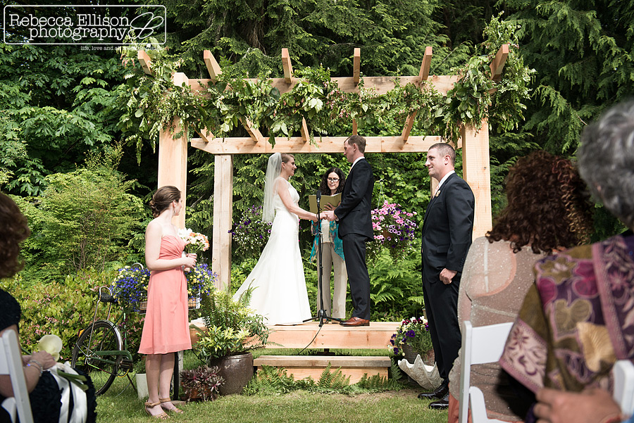 bride and groom hold hands during wedding ceremony in backyard