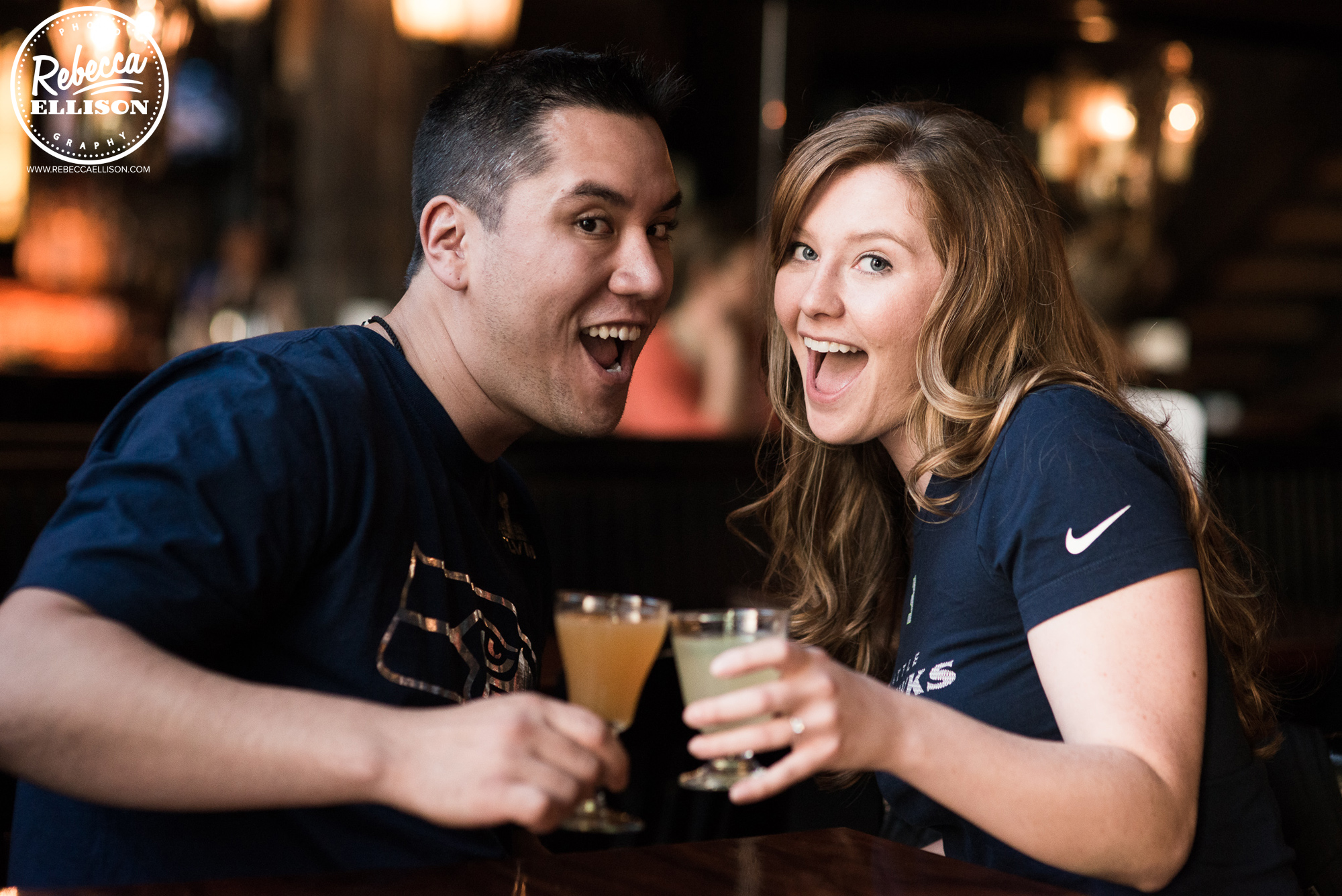 Engagement portraits featuring cocktails and Seahawks T-shirts photographed in downtown Ballard by Rebecca Ellison Photography