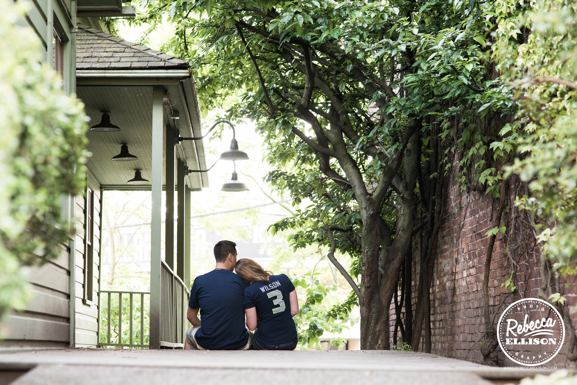 An engaged couple wearing Seahawks t-shirts sits on their porch during an outdoor rural engagement session photographed by Rebecca Ellison photography