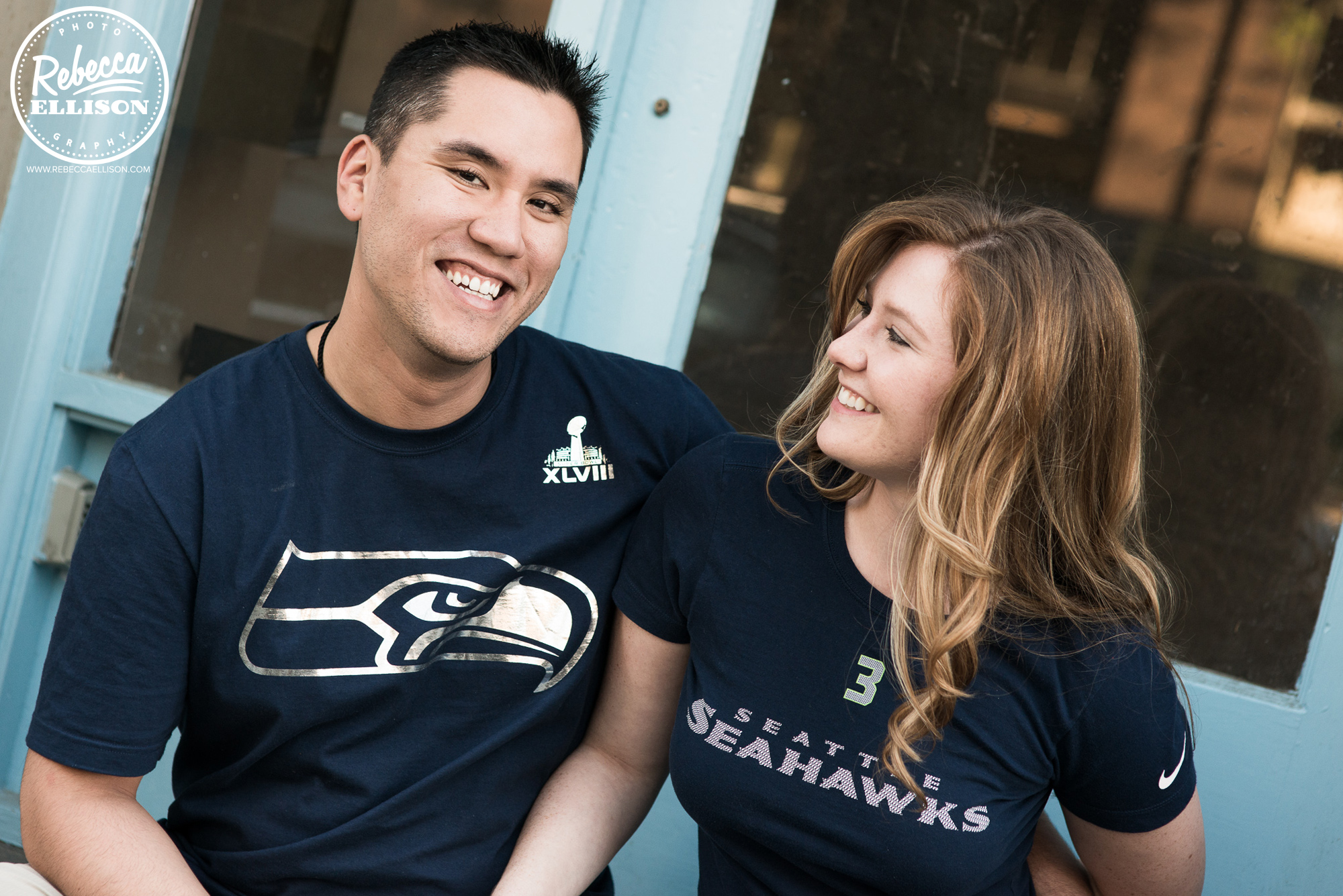 A couple wearing Seahawks t-shirts celebrates their engagement during outdoor engagement photos by Ballard engagement photographer Rebecca Ellison