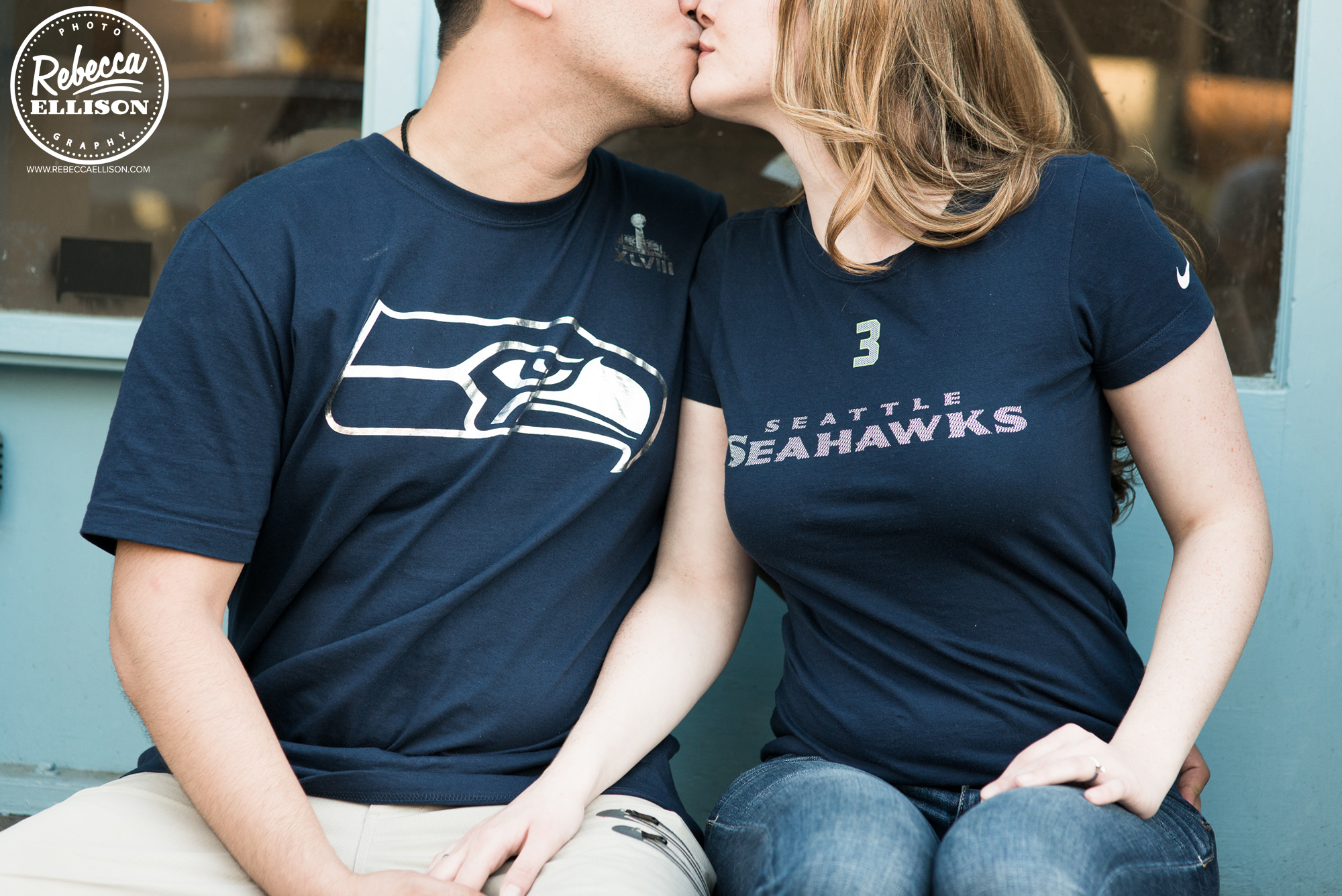 A couple wearing Seahawks shirts during their engagement portraits kisses photographed by Rebecca Ellison Photography