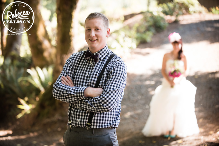 chess-inspired-wedding- groom in black and white checkered shirt and bowtie with bride approaching in background