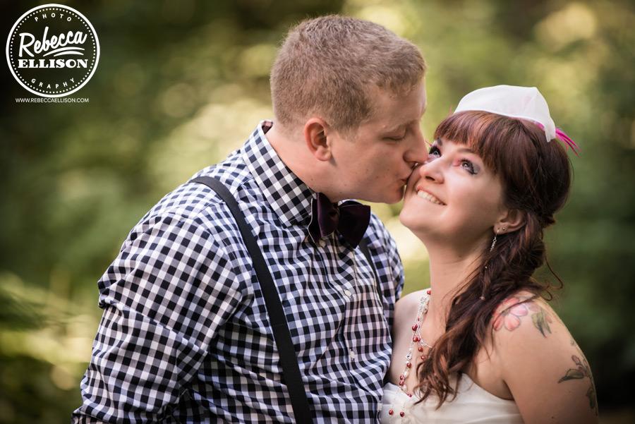 chess-inspired-wedding-006 groom wearing checkered shirt, purple bowtie and suspenders, bride has side braid wedding hair and birdcage viel
