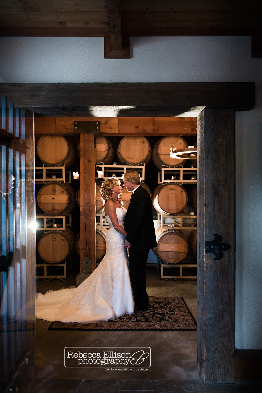 bride and groom in a wine cellar at delille cellars wedding photographed by Seattle wedding photographer Rebecca Ellison