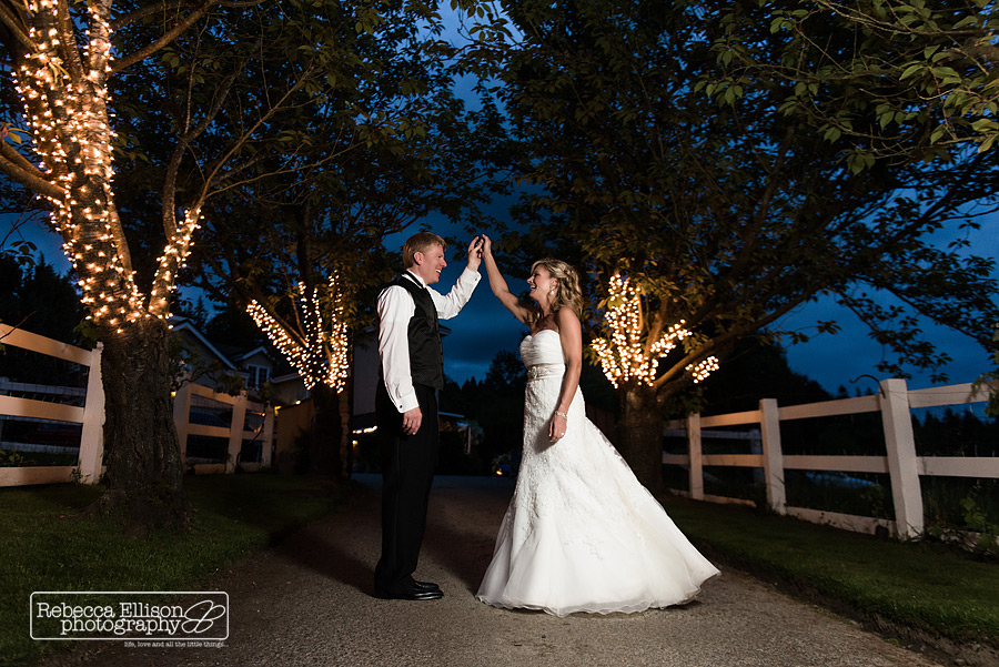 evening portrait of bride and groom at DeLille Cellars wedding standing in a tree lined pathway photographed by Rebecca Ellison Photography