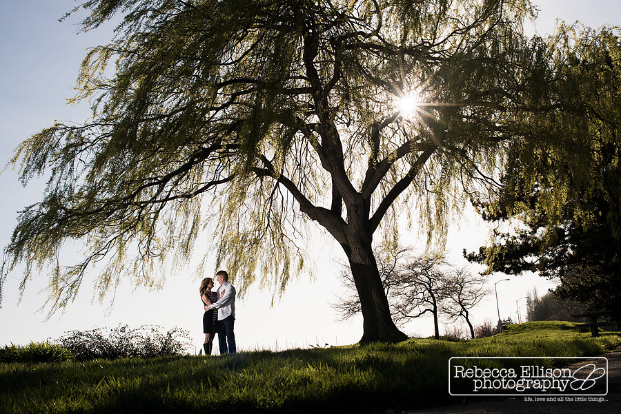A couple stands under a large tree in the sunshine during their outdoor engagment portrait session by Seattle engagement photographer Rebecca Ellison
