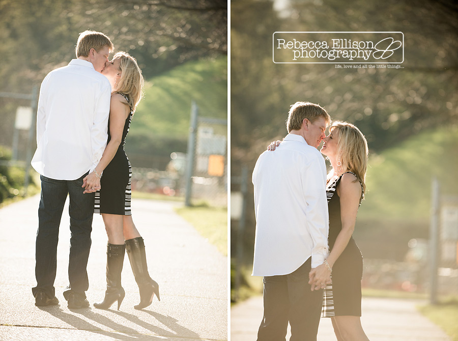A couple kisses as they walk down a path during their Smith Cove Park Engagement portraits with Seattle engagement photographer Rebecca Ellison