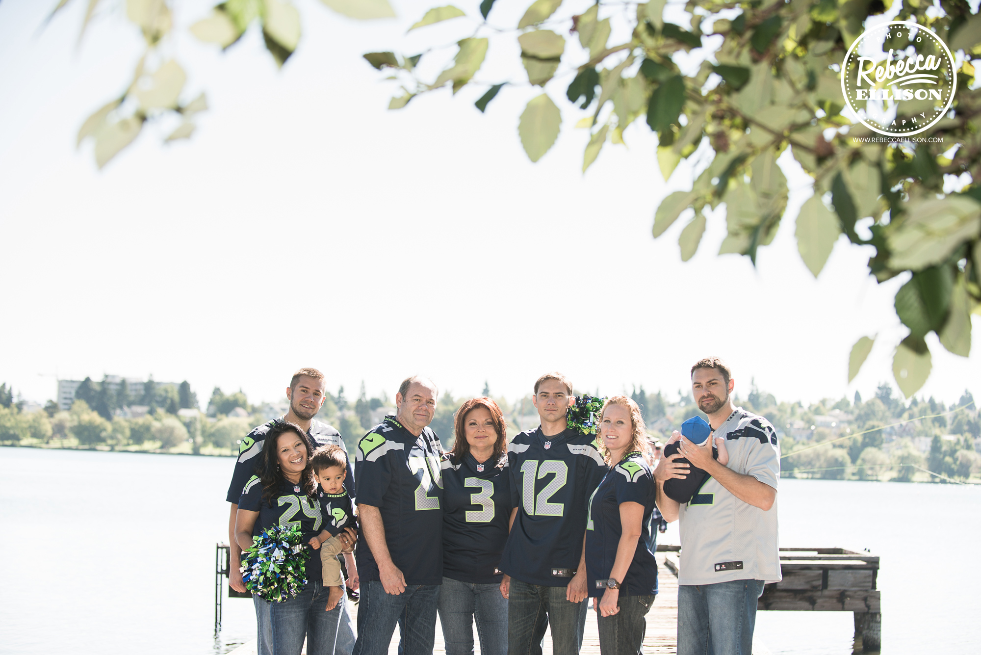 An extended family of Seahawks fans poses for family portraits at Greenlake park wearing their Seahawks jerseys photographed by Seattle family photographer Rebecca Ellison