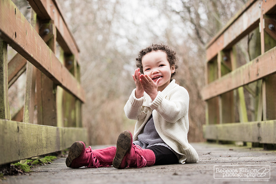 A 2 year old sits on a wooden bridge and claps her hands during winter outdoor family portraits by Rebecca Ellison Photography