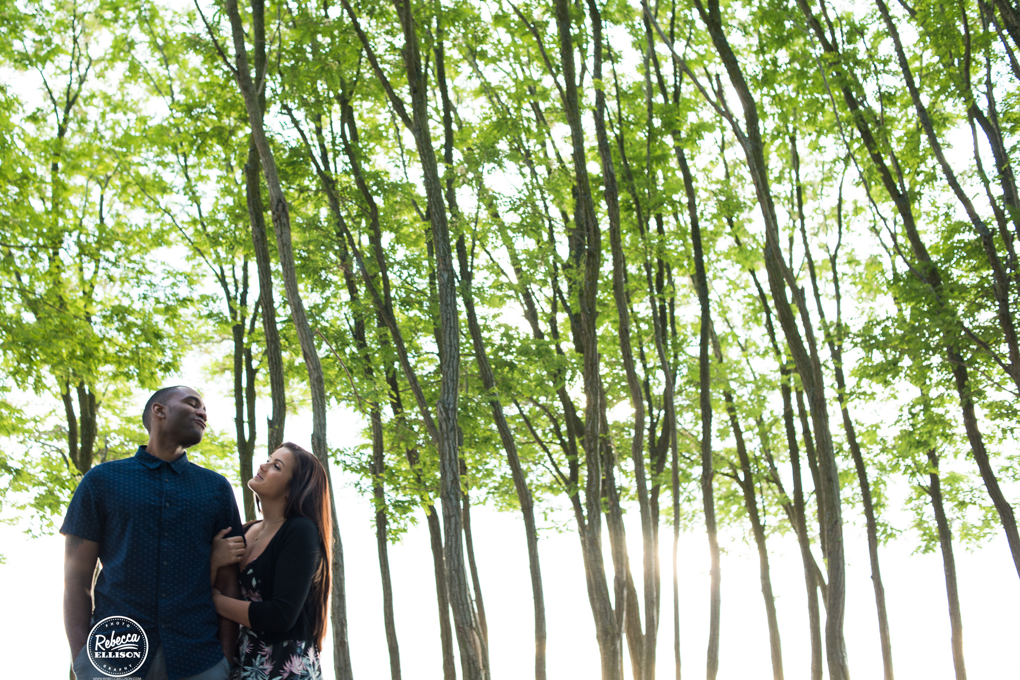 Engaged couple stand in front of trees in an outdoor engagement session photographed by Seattle wedding photographer Rebecca Ellison