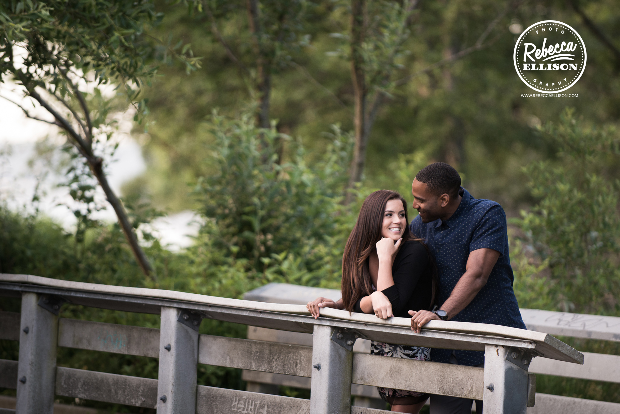 Outdoor engagement session couple stands on a bridge at Golden Gardens in Seattle photographed by Rebecca Ellison