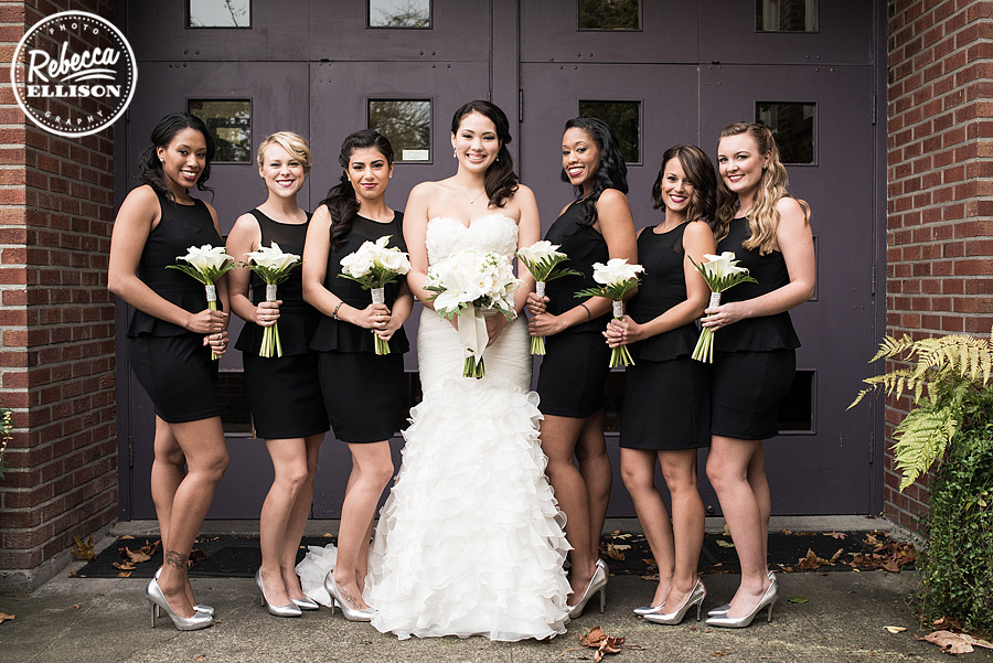 bride and bridesmaids at an elegant black, white and red wedding featuring a strapless ruffled wedding dress and black bridesmaid's dresses at the hall at fauntleroy photographed by seattle wedding photographer rebecca ellison
