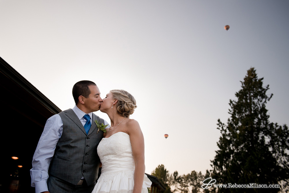 Snohomish Wedding Photographer Rebecca Ellison capture sunset portrait of bride and groom kissing outdoors of farm wedding venue Hidden Meadows with hot air balloons in background