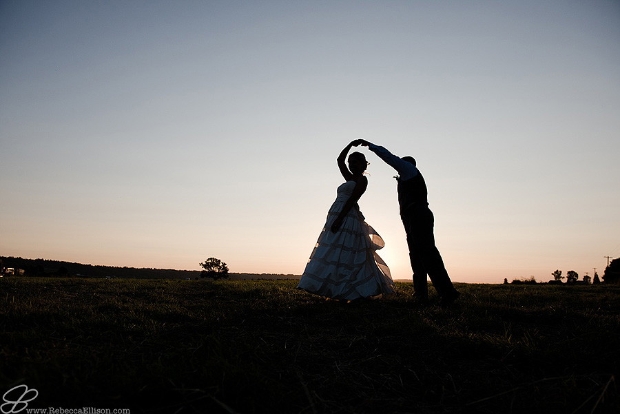 Snohomish wedding photographer Rebecca Ellison captures silhouette of groom twirling bride in a field during sunset outside of Hidden Meadows wedding venue.