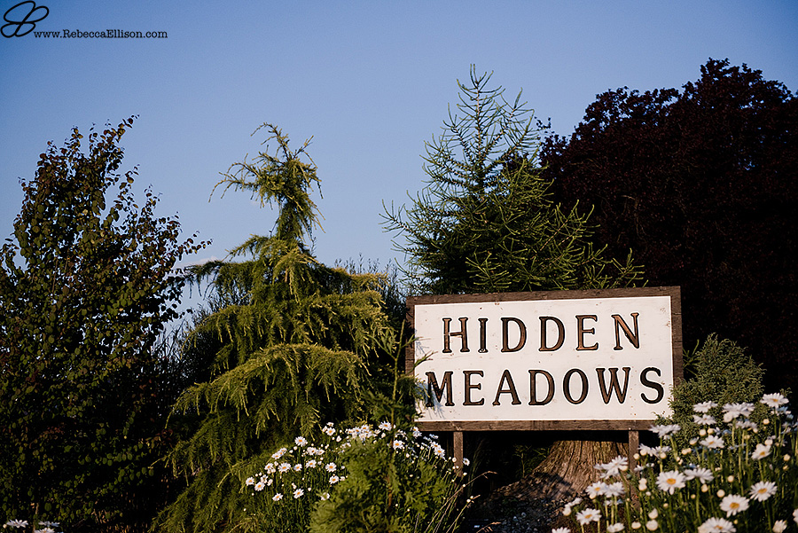 Snohomish wedding photographer Rebecca Ellison captures sign at the front of Hidden Meadows outdoor barn wedding venue.
