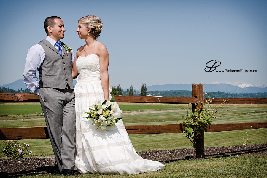 Snohomish wedding photographer Rebecca Ellison captures outdoor portrait of bride and groom by wooden fence with fields and Olympic mountains in background at Hidden Meadows wedding venue. Groom wearing grey suit and bride wearing strapless gown from Belltown Bride.