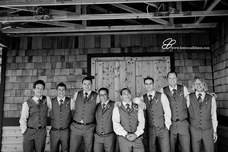 Snohomish wedding photographer Rebecca Ellison captures black and white image of groom and groomsemen at Hidden Meadows in front of wooden doors. Groom wearing grey tux with vest and blue tie from the Tuxedo Club