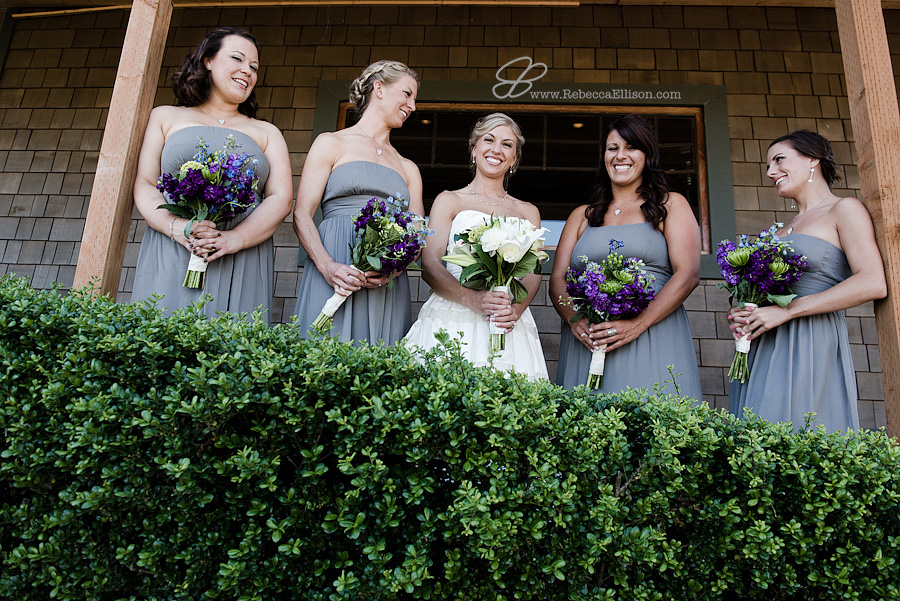 Snohomish wedding photographer Rebecca Ellison captures photo of bride and bridesmaids at Hidden Meadows. Bride wearing dress from Belltown Bride and bridesmaids in strapless grey knee length dresses