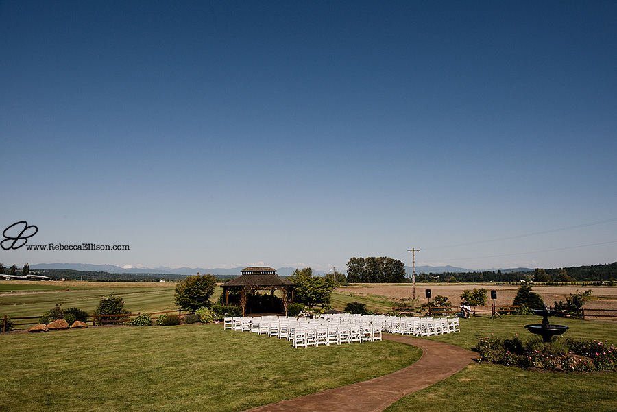 Snohomish wedding photographer Rebecca Ellison captures detail of the outdoor summer wedding ceremony at Hidden Meadows with mountains and blue sky in the background.