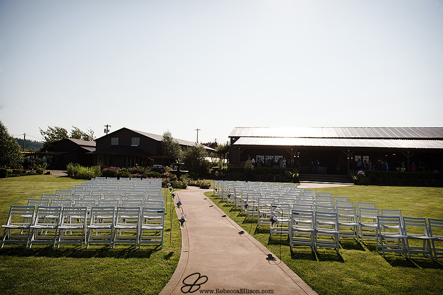 Snohomish wedding photographer Rebecca Ellison captures detail image of wedding ceremony set up for outdoor summer wedding with white chairs at Hidden Meadows wedding venue with the barn in the background