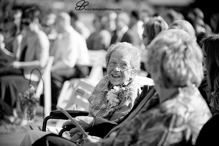 Snohomish wedding photographer Rebecca Ellison captures black and white candid image of a grandma smiling during outdoor summer wedding ceremony at Hidden Meadows wedding venue.