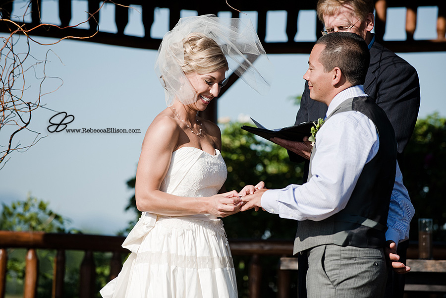Snohomish wedding photographer Rebecca Ellison captures bride putting ring on grooms finger during outdoor summer wedding ceremony at Hidden Meadows wedding venue.