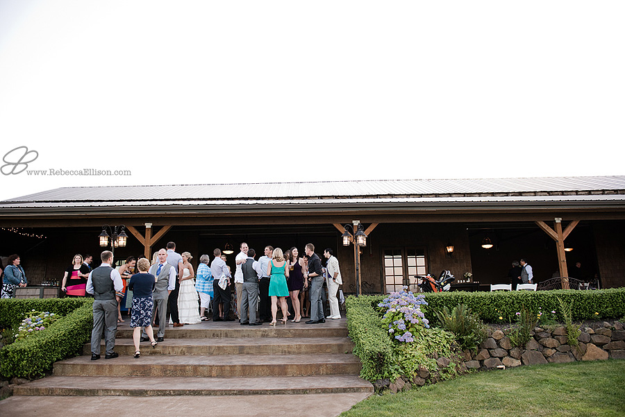 Snohomish wedding photographer Rebecca Ellison captures overall image of guests mingling during cocktail hour outdoors at Hidden Meadows wedding venue