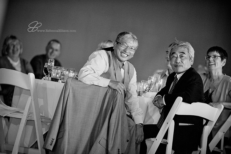 Snohomish wedding photographer Rebecca Ellison captures candid black and white photo of the father of the groom laughing during wedding toasts at Hidden Meadows wedding venue