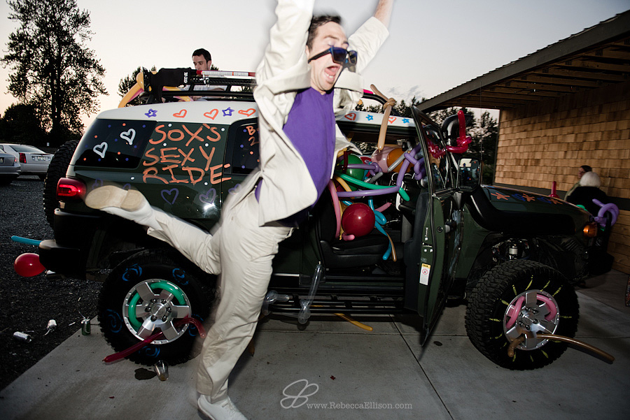 Snohomish wedding photographer Rebecca Ellison captures candid moment of guest jumping in front of decorated car at a wedding at Hidden Meadows Snohomish wedding venue