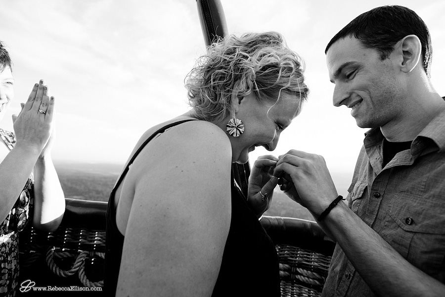 girl says yes during surprise wedding proposal in hot air balloon with Seattle in the background by Seattle wedding photographer Rebecca Ellison Photography