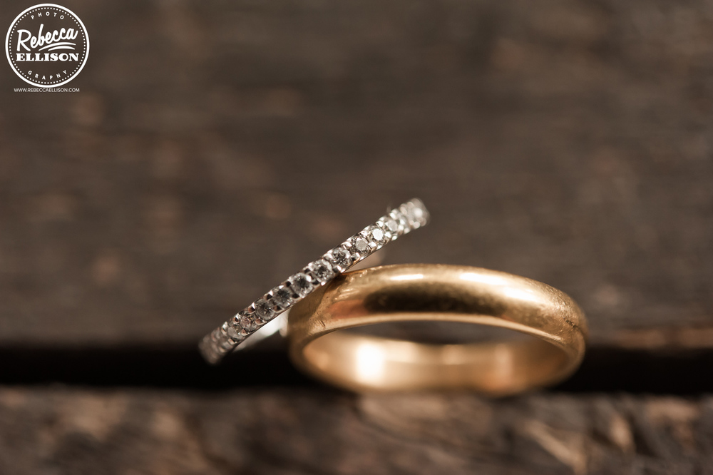 Wedding Rings sit on a rough wooden floor photographed by Seattle wedding photographer Rebecca Ellison